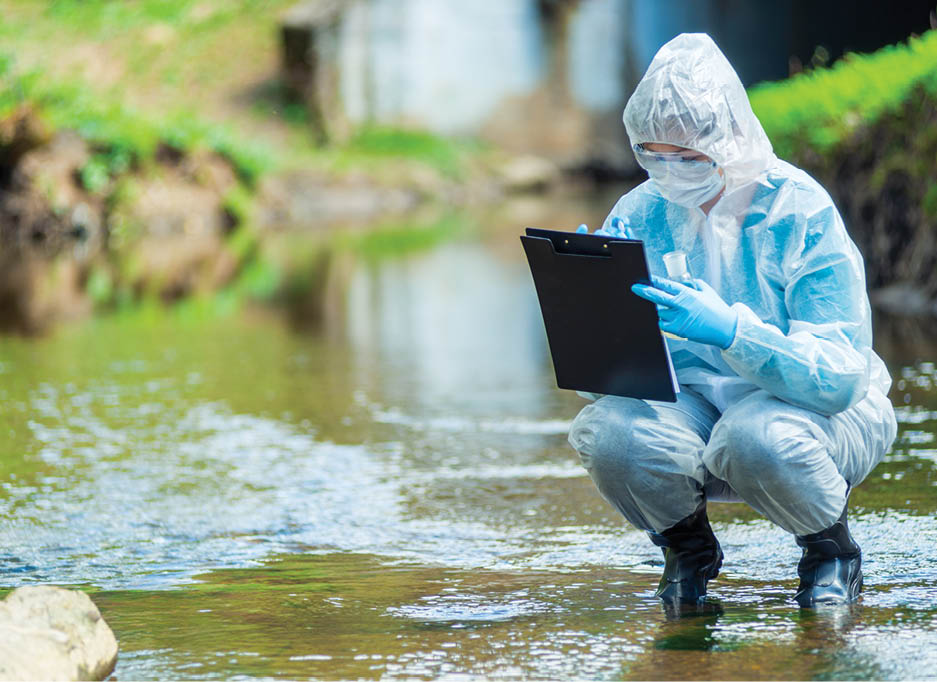 Ecosystems: A scientist recording observations in a shallow stream